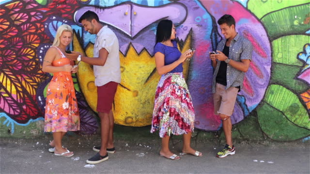 Brazilian friends lean against graffitied wall and text on smartphones