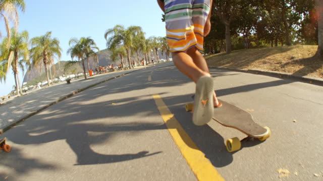 vídeos de stock, filmes e b-roll de brazilian friends skateboard up beachfront street in slow motion with sugarloaf in distance - andar de skate