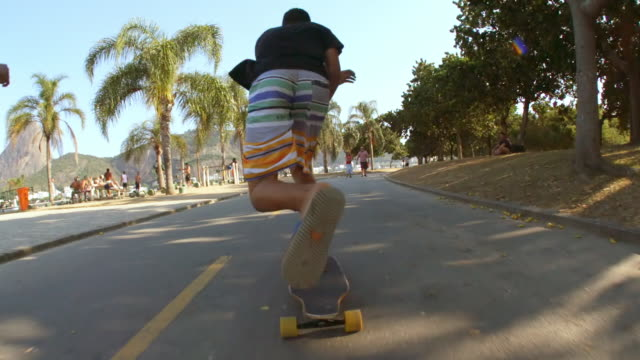 brazilian friends speed up beachfront street on skateboards with sugarloaf in distance - longboarding stock videos & royalty-free footage