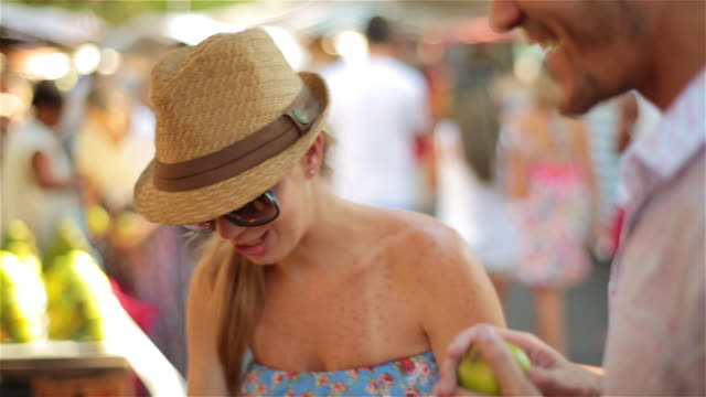 Brazilian girl picks out fruit at farmers market and hands off to boyfriend