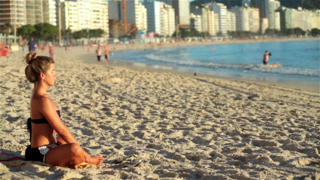 brazilian girl practices yoga on copacabana beach - posture stock videos and b-roll footage