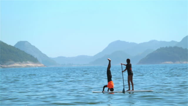 Brazilian girl steers paddleboard as boy does headstand off Copacabana shore