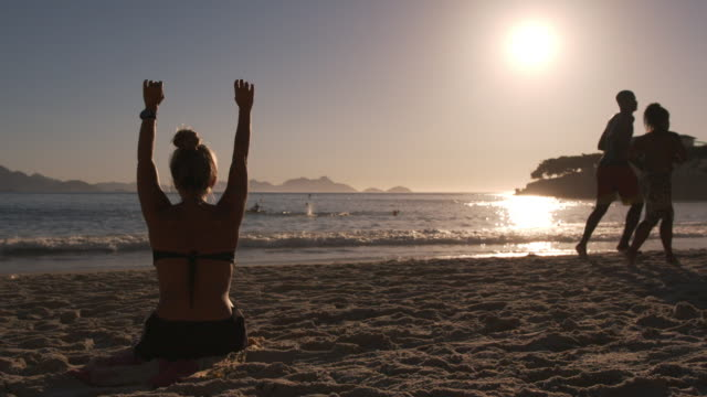 Brazilian girl stretching on Copacabana Beach raises arms, bends forward, and leans side to side in the sun and sand