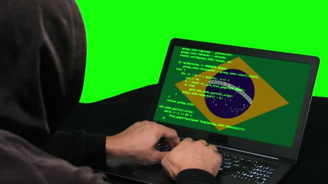 brasilianische hacker typisieren code hacking auf seinem laptop mit brasilianischer flagge auf dem grünen bildschirm hintergrund - schwarzes hemd stock-videos und b-roll-filmmaterial