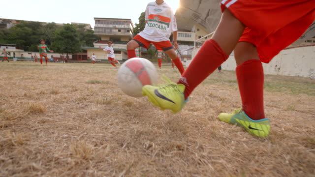 brazilian kid in jersey kicks soccer ball during scrimmage on barren soccer field - international soccer event stock videos & royalty-free footage