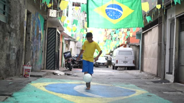 vídeos de stock e filmes b-roll de brazilian kid playing soccer in the street - brazilian ethnicity