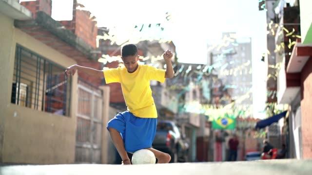 vidéos et rushes de brésilien kid jouer au soccer dans la rue - brésilien