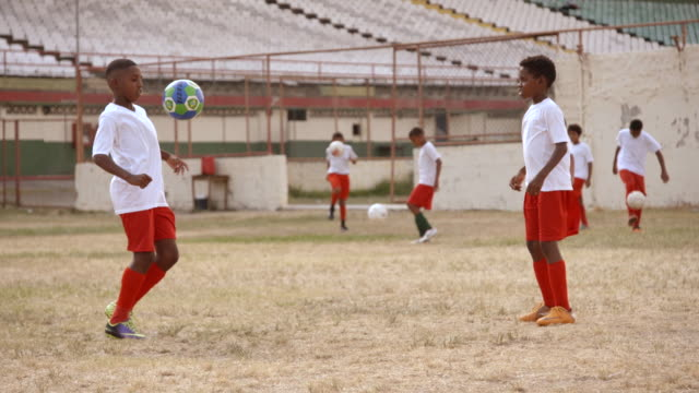 Brazilian kids practice juggling and passing soccer ball in old soccer stadium