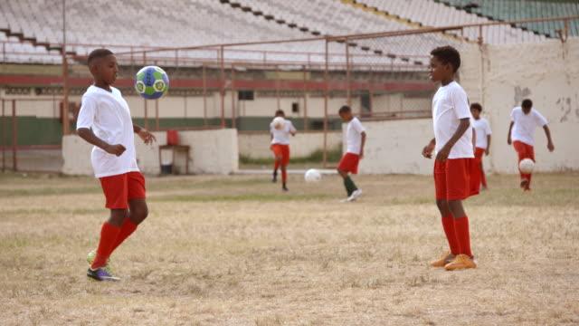 vidéos et rushes de brazilian kids practice juggling and passing soccer ball in old soccer stadium - délabré