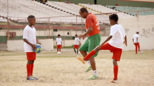 Brazilian man coaches youth soccer players on old stadium field