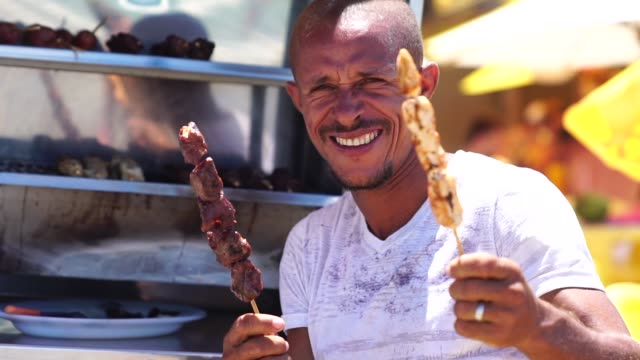 brazilian man holding bbq on a stick on the beach - south america stock videos & royalty-free footage
