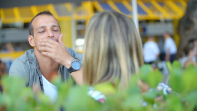 Brazilian man listens to girlfriend and wipes his brow at outdoor restaurant