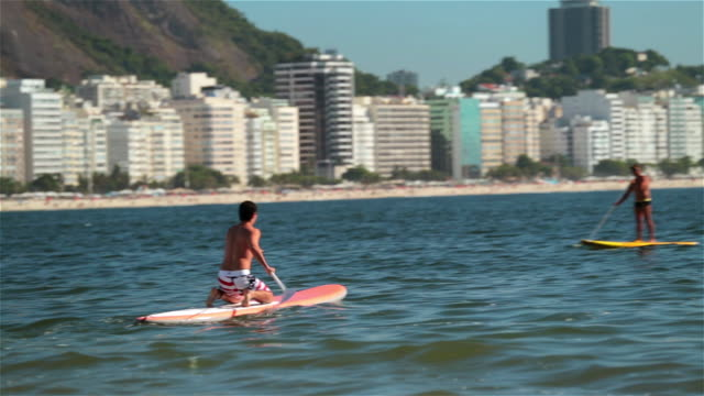 brazilian man paddles surfboard on his knees across scenic copacabana bay - board shorts stock videos and b-roll footage