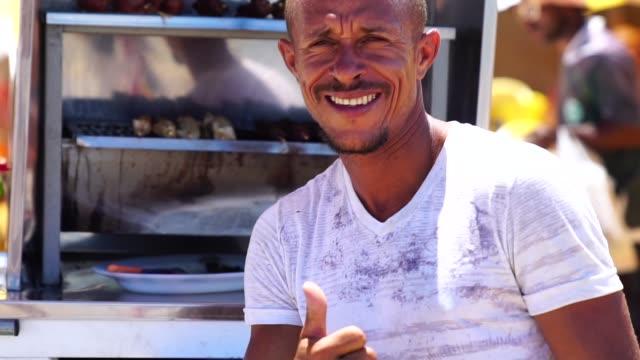 vídeos y material grabado en eventos de stock de hombre brasileño prepara barbacoas en la playa - bahía