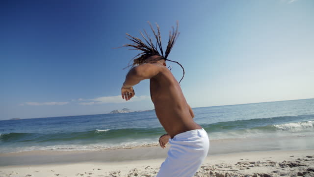 vídeos de stock e filmes b-roll de brazilian martial artist jumps up and slams palm into sand on ipanema beach, claps and jabs fist at camera - elbow