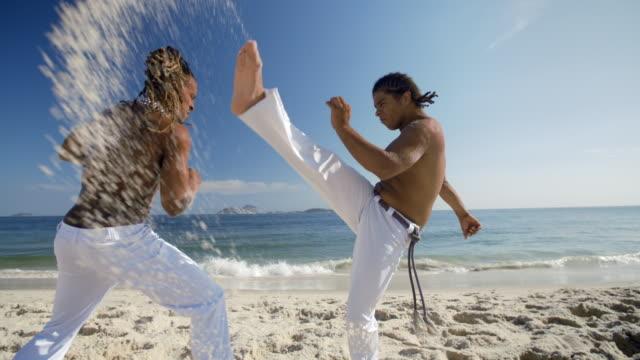 Brazilian martial artist kicks over opponent's head sending barrage of sand at camera on Ipanema Beach