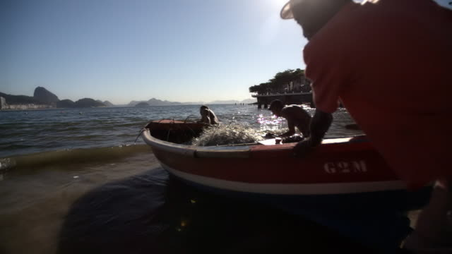 brazilian men launch fishing boat into surf from copacabana beach in slow motion - surf fishing stock videos & royalty-free footage