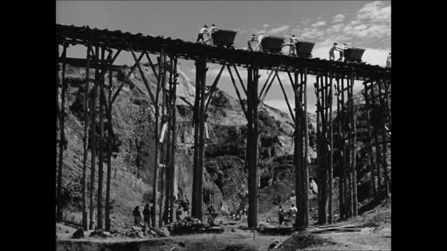 vídeos de stock e filmes b-roll de brazilian miners pushing rail carts across bridge over mines ms workers loading rail ore into railcar ls train full of ore moving through mountain... - 1944