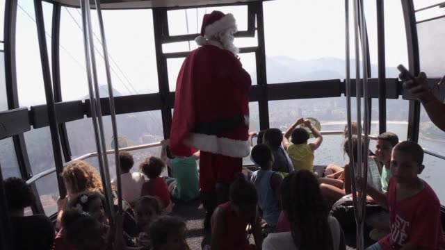 a brazilian ngo takes children in need up rio de janeiros sugar loaf mountain with a santa claus impersonator - esporte stock videos and b-roll footage