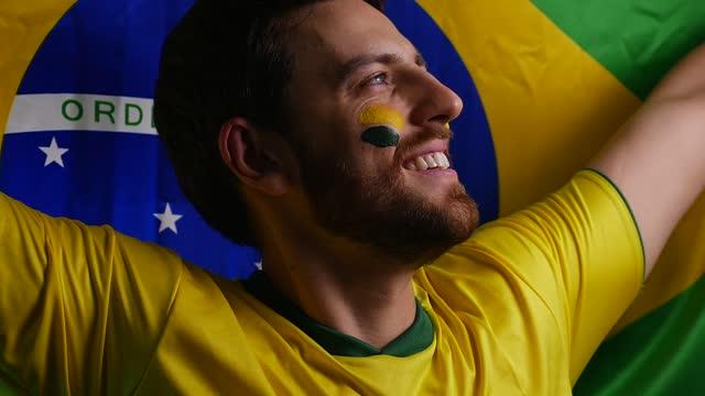 vídeos de stock, filmes e b-roll de patriótico brasileiro segurando a bandeira nacional - bandeira