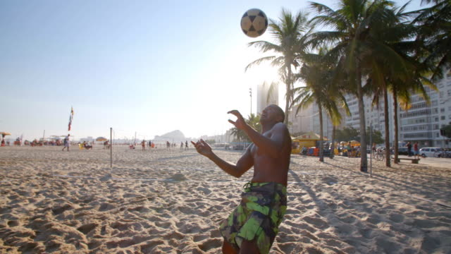 brazilian player braces himself and heads soccer ball over net in beach footvolley match - competition round stock videos and b-roll footage