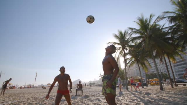 brazilian player sets up partner to head soccer ball over net in beach footvolley match - internationaler fußball stock-videos und b-roll-filmmaterial