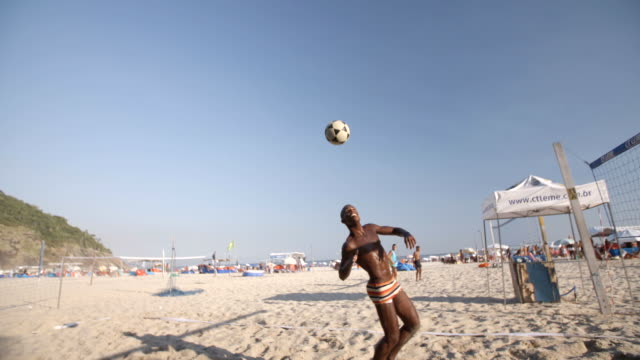 Brazilian player sets up partner to head soccer ball over net in beach footvolley match