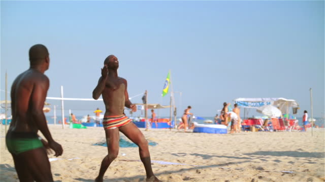 Brazilian player shoulders ball to partner who sets him up for dynamic header in beach footvolley match