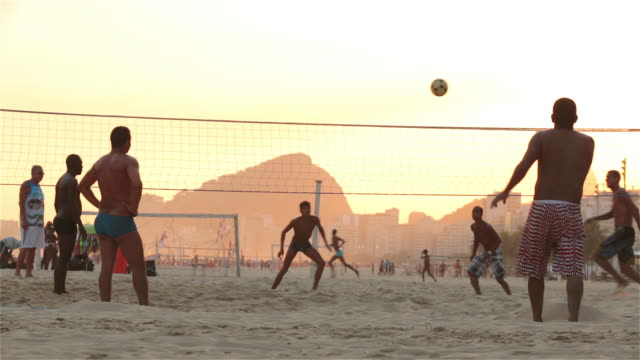brazilian players serve, kick and head soccer ball over net in beach footvolley match - 蹴る点の映像素材/bロール