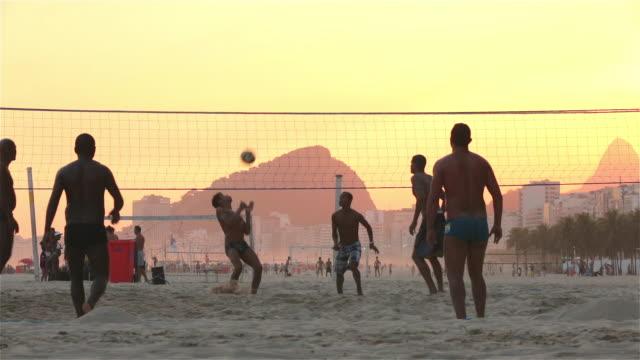 vídeos de stock, filmes e b-roll de brazilian players serve, kick and head soccer ball over net in beach footvolley match - campeonato esportivo