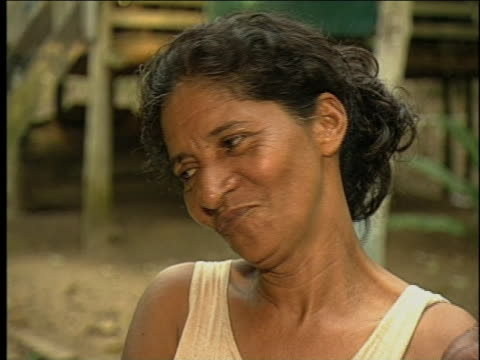 a brazilian pours assai juice into a glass with a ladle as a woman smoking a cigarette laughs - ladle stock videos & royalty-free footage