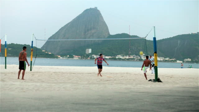 Brazilian soccer players volley ball back and forth on Botafogo beach with Sugarloaf in background