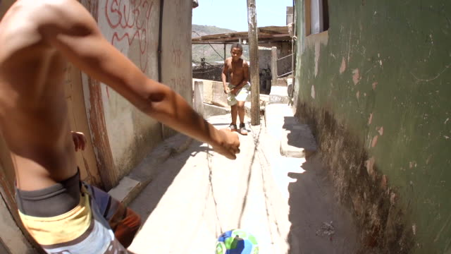 vídeos de stock, filmes e b-roll de brazilian street kids dribble soccer ball through stone alley, smile and make peace signs at camera - tronco nu