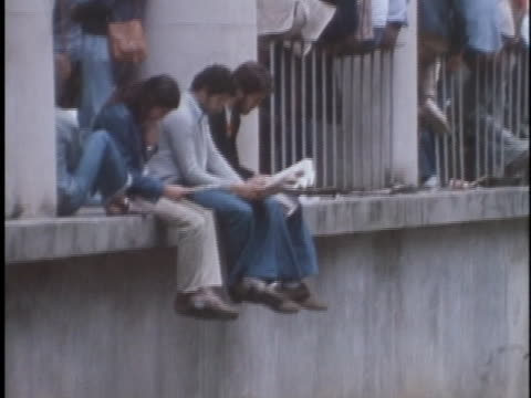 vídeos de stock, filmes e b-roll de brazilian students attending a rally against government oppression sit on a balcony ledge - human rights or social issues or immigration or employment and labor or protest or riot or lgbtqi rights or women's rights