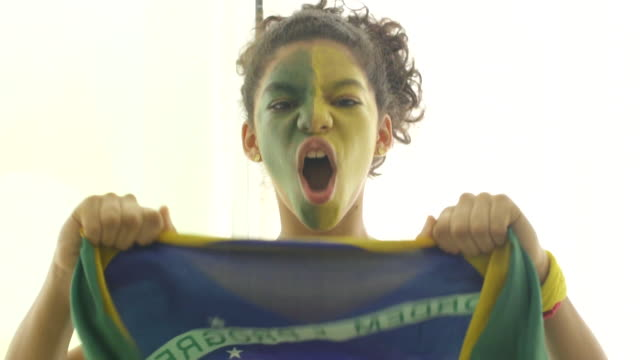 brazilian supporter with painted face waving brazilian national flag - avvenimento sportivo video stock e b–roll