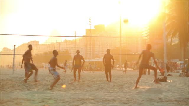brazilian team kicks and heads soccer ball over net and scores point in heated footvolley match - internationaler fußball stock-videos und b-roll-filmmaterial
