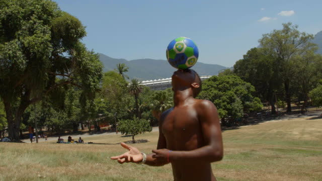 vídeos de stock, filmes e b-roll de brazilian teen balances soccer ball on forehead on hillside overlooking world cup stadium - stunt
