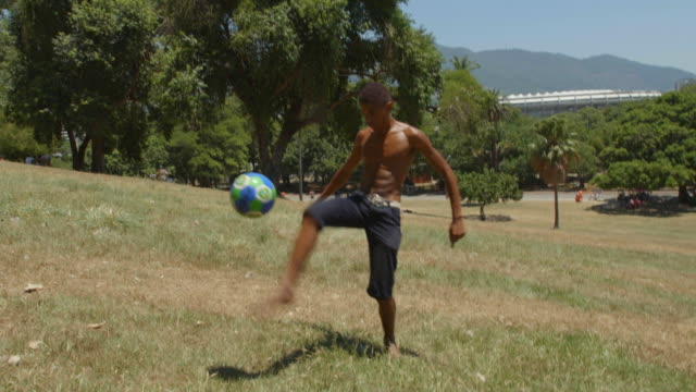 brazilian teen juggles and heads soccer ball at camera on hillside overlooking maracana stadium - jonglieren stock-videos und b-roll-filmmaterial