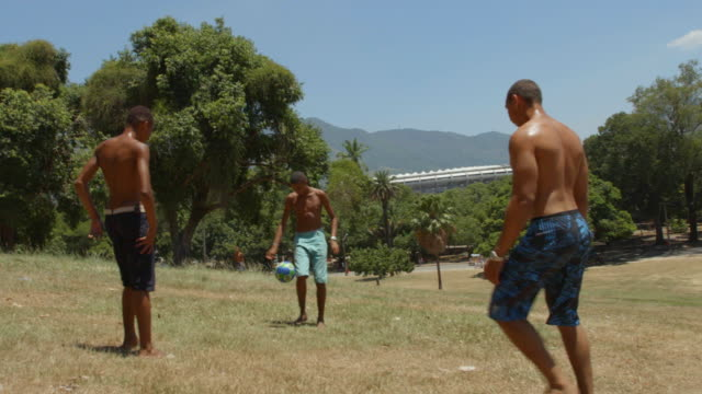 vídeos de stock, filmes e b-roll de brazilian teen juggles soccer ball with friends on hillside overlooking world cup stadium - proeza acrobática