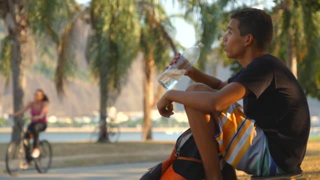 Brazilian teen sits on skateboard and drinks water bottle by Guanabara Bay