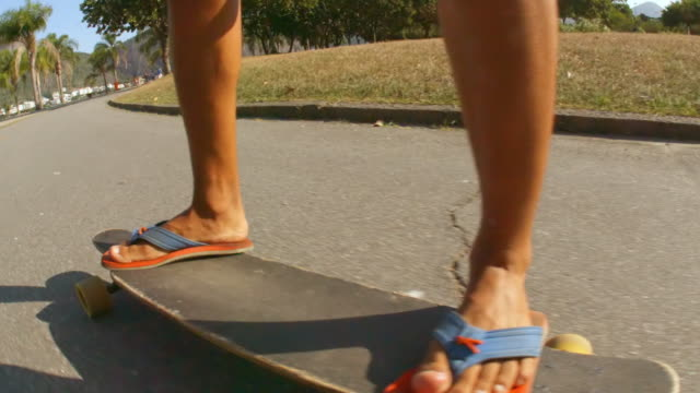 Brazilian teen walks back and forth changing stances on skateboard