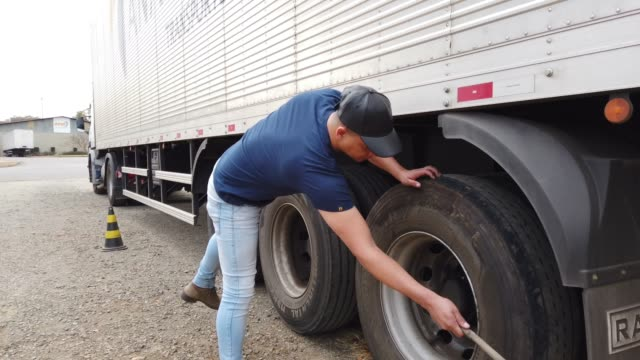 brazilian truck driver checking the tires of his semi truck. - commercial land vehicle stock videos & royalty-free footage