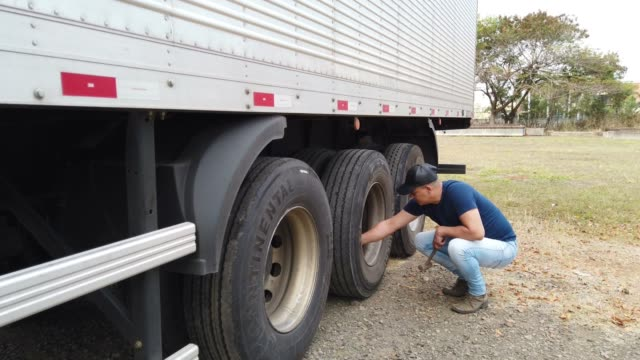 brazilian truck driver checking the tires of his semi truck. - trucker cap stock videos & royalty-free footage
