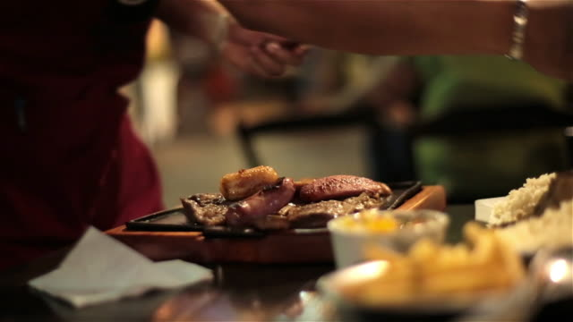brazilian waiter serves meat from skillet to customer's plate in rio restaurant - dining stock videos & royalty-free footage