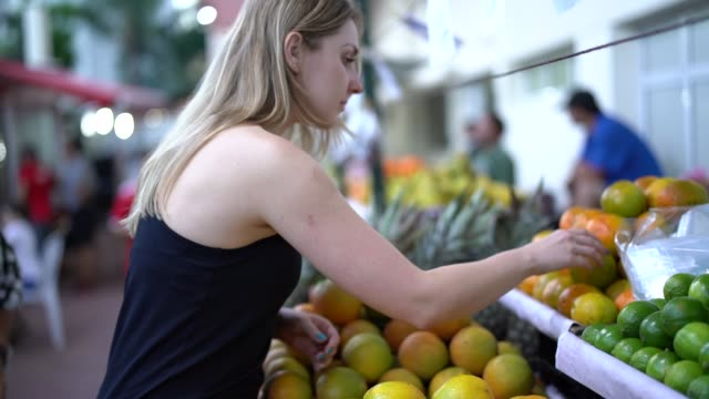 brazilian woman buying fruits on street market - agricultural fair stock videos & royalty-free footage