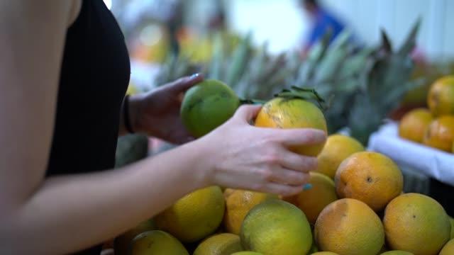 vídeos de stock, filmes e b-roll de mulher brasileira comprando frutas no mercado de rua - vendendo