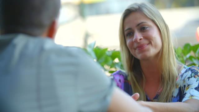 Brazilian woman listens to boyfriend and laughs at outdoor restaurant