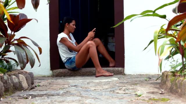 Brazilian woman sitting at house entrance