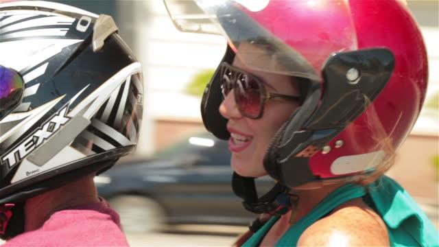 brazilian woman smiles on back of mototaxi speeding through the streets of rio - ドレス点の映像素材/bロール