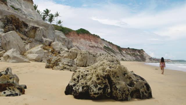 ws brazilian woman walking down empty beach / trancoso, brazil - porto seguro stock videos & royalty-free footage